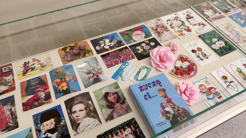 Zdjęcie kolorowe, fragment wystawy kartek pocztowych w holu biblioteki